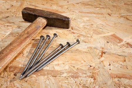 osb: Hammer and nails over hardboard background