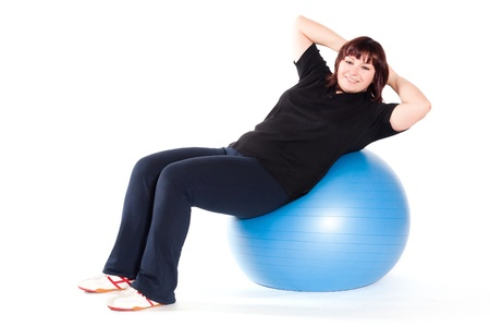 Shot of a overweight young woman exercise on fitness ball against white background. Stock Photo