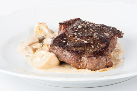 rib steak with sauteed mushrooms and onions, french fries and vegetables photo