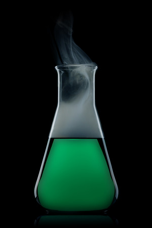 flask with green liquid to the black background  Stock Photo