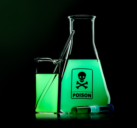 flask with green liquid to the black background  photo