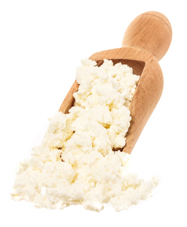 Cottage cheese in a wooden spoon isolated on white background