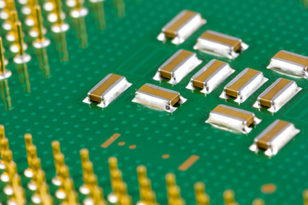 Small SMD capacitors on green processor with golden pins. photo