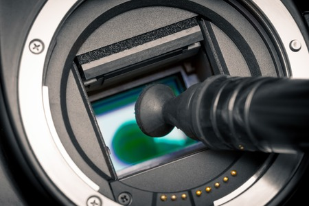 Image photo sensor being cleaned with a lens pen. DSLR APS-C. photo