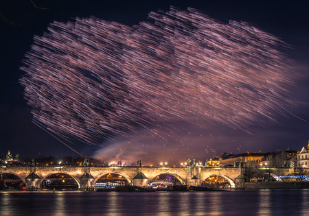 A fireworks show is staged near the historical Charles Bridge in the centre of Prague, with reflections in water.