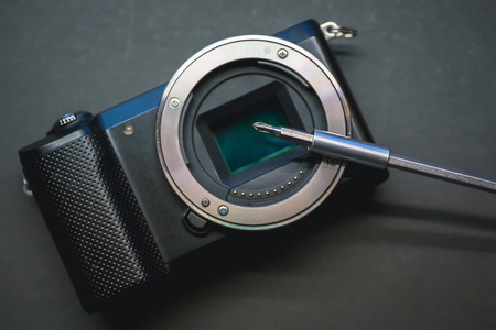 Mirrorless camera sensor repair, screwdriwer over lens mount. Shot from above.