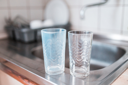 Dirty and clean glass cups on a kitchen sink. Broken washing machine concept.