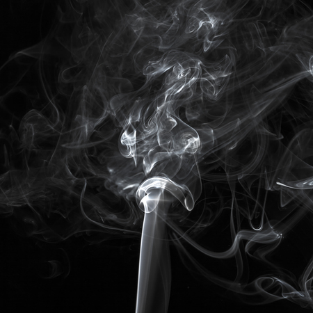 Abstract white smoke swirls pattern over the black background