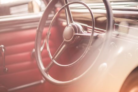 Classic vintage car interior, close up on steering wheel, dasboard, retro effect