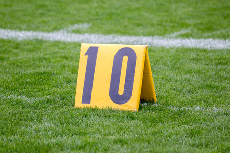 American Football 10 yard marker on grass by the line