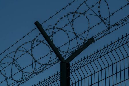 Barbed wire steel fence against the immigrants in europe. Restricted area at night. Stockfoto