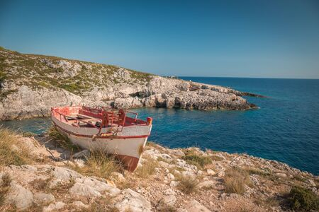 The old abandoned wooden fishing boat on a rocky cliff shore on a sunny day in greece , Zakynthos.