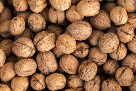 Walnuts. Whole walnuts background. Many walnuts close-up. Walnut texture. Reklamní fotografie - 132125982