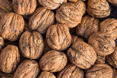 Walnuts. Whole walnuts background. Many walnuts close-up. Walnut texture. Reklamní fotografie - 132126468