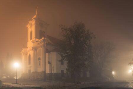 Old Church in fog at night, St. Gotgard Church in Cesky Brod, central bohemia region czech republic. Spooky autumn or winter scene.