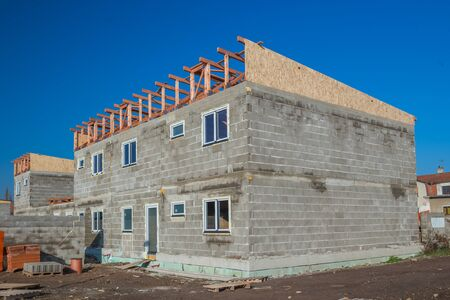 House under construction. Workers installing fibreboard on the roof Stock Photo