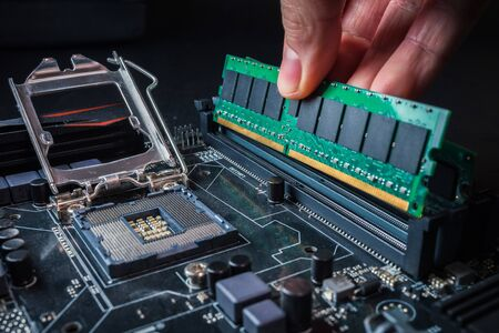 Electronic engineer of computer technology. Maintenance computer hardware upgrade of motherboard putting the Ram on the motherboard computer. Concept of PC memory upgrade.