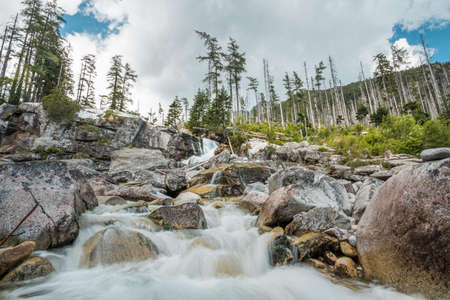 Waterfalls of Cold stream in Great Cold Valley in High Tatras, Slovakia. Cloudy sky.
