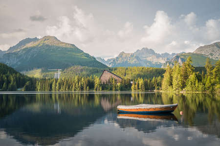 Mountain lake Strbske Pleso with small boat in the foreground in National Park High Tatras. Slovakia, Europe. Late summer evening at lakeside. Standard-Bild