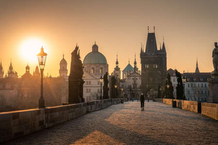 PRAGUE, CZECH REPUBLIC, APRIL 2020 - Man in respirator during covid lockdown, Charles bridge at sunrise, Old Town bridge tower, Prague UNESCO, Czech republic, Europe - Old town
