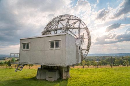 Satellite dish in a summer landscape, radiotelescope for deep space research. Ondrejov observatory, Czech republic.