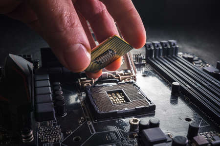 Technician plug in CPU microprocessor to motherboard socket. Workshop background. PC upgrade or repair concept. Imagens