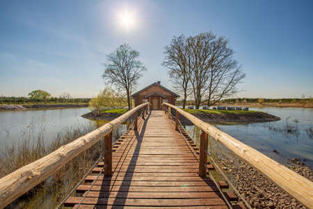 June 2020, Kosice, Czech republic - In the middle of the lake there is a house in a small grove, a wooden bridge with railings leads to it. The water is calm, the sky is blue and clear. Editorial