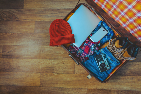 open suitcase: Open suitcase with casual clothes, laptop and phone Stock Photo