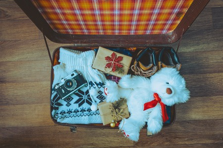 open suitcase: Open suitcase with casual clothes and gifts for christmas Stock Photo