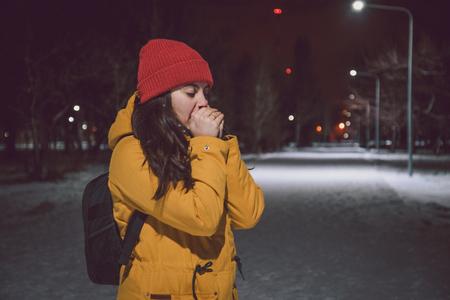 frozen winter: woman frozen in night winter snow park