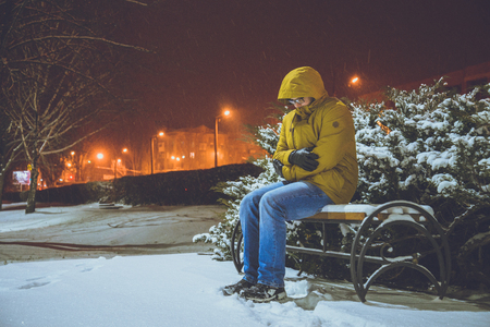 Man sitting on a bench in cold winter night frozen