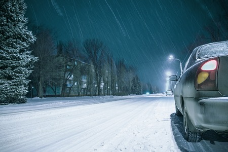 winter night road snow background with car lights