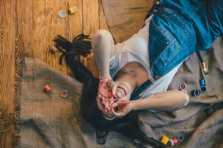 flor: Woman lying on the floor paint all over her Stock Photo