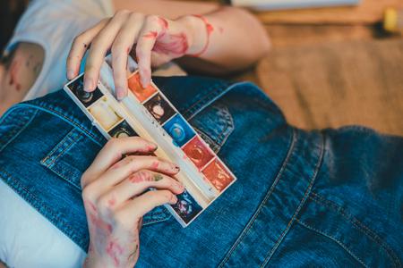 girl lying studio: Woman lying on the floor paint all over her Stock Photo