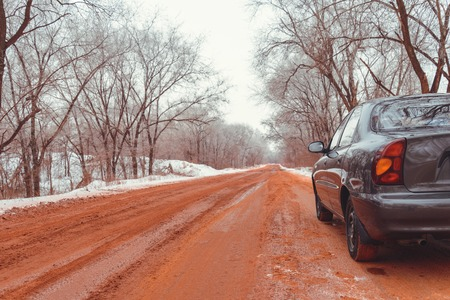 winter tires: lonely car road in snow red because of ore