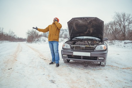 upset young men look under the hood and call service
