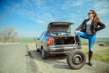 woman rolls car wheel Imagens