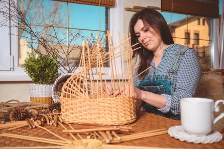 basketry: young pretty woman making baskets