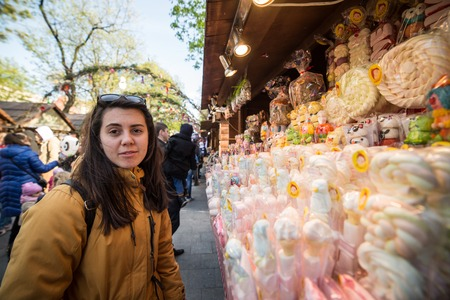 Woman tourist chooses candy at outside market