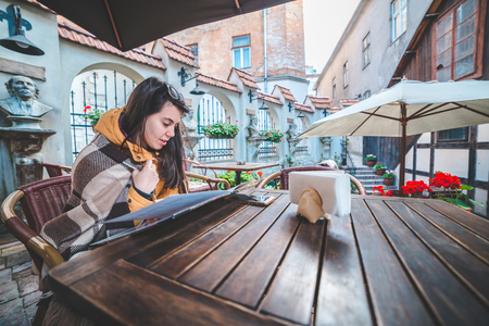 Young beautiful woman order food in outdoor cafe in chill morning
