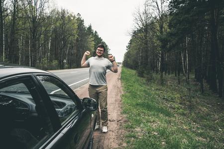 yang man stratching near car after long road Stock Photo