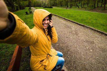 Cute happy young woman taking selfie in windy day Stock Photo