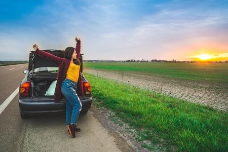 woman stratching near car long car trip Stock Photo