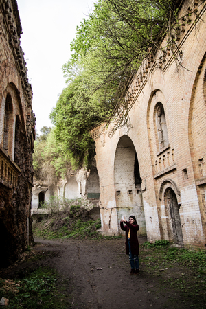 take a history: Young woman tourist photographing old ruins