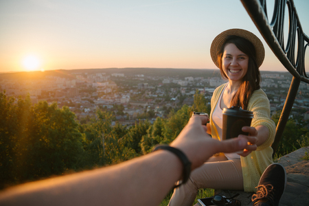 Female giving coffee to man while they sitting on the hill on sunrise Stock Photo