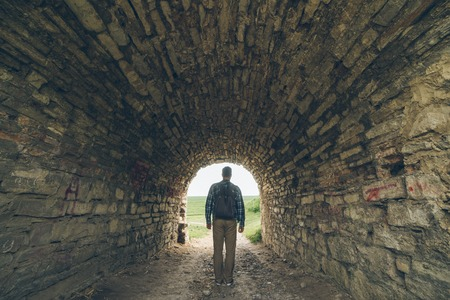 lighted: man stands in old castle tunnel