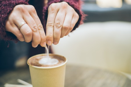 woman hands pouring suger to the latte cup Stock Photo
