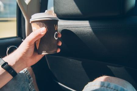 man passenger drink coffe in car Фото со стока
