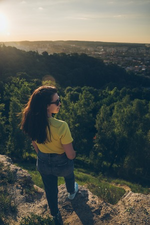 young woman with long dark hair on the peak of the hill Stock Photo