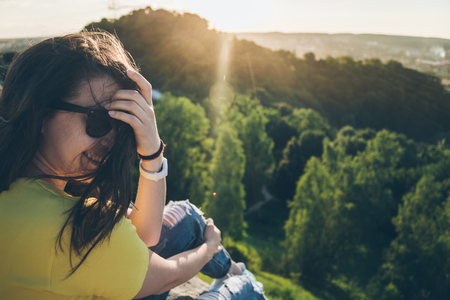 jill: young pretty woman sitting and smiling on the top of the hill Stock Photo